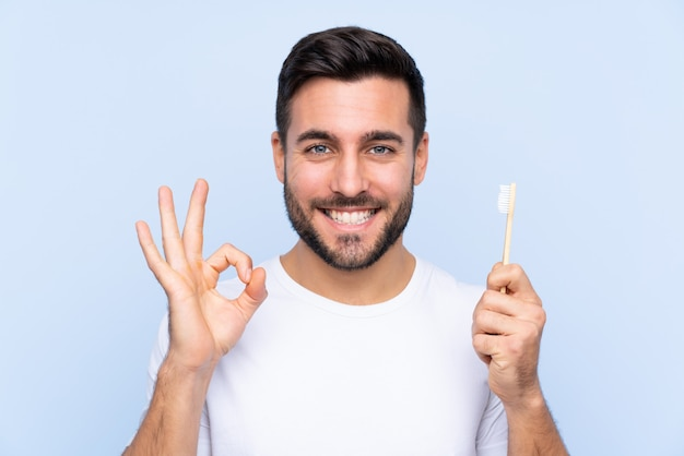 Man with toothbrush over isolated blue wall