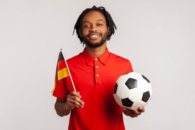 Человек с зубастой улыбкой держит флаг германии и футбольный мяч и смотрит матч.