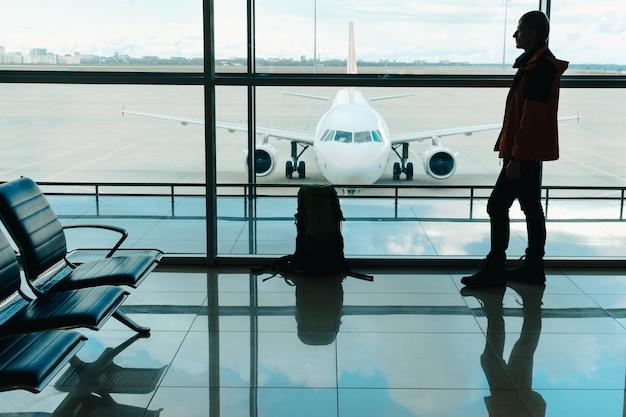 窓の近くの空港ターミナルのラウンジで搭乗を待っている旅行のバックパックを持つ男