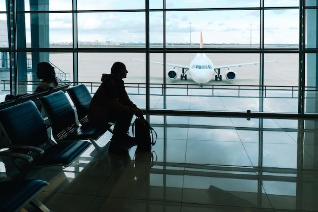 空港ターミナルのラウンジで搭乗を待っている旅行のバックパックを持つ男