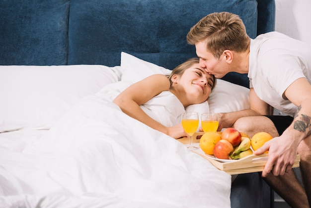 Man with tray of food kissing sleeping woman on forehead