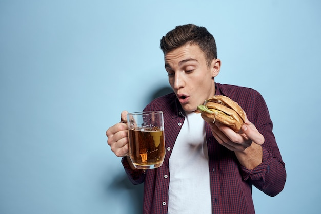 Man with a tray of junk food: hamburger and french fries, beer