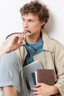 本を持っているトレンチコートを持つ男