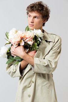 Man with trench coat holding flowers
