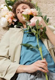 꽃을 들고 트렌치 코트를 가진 남자