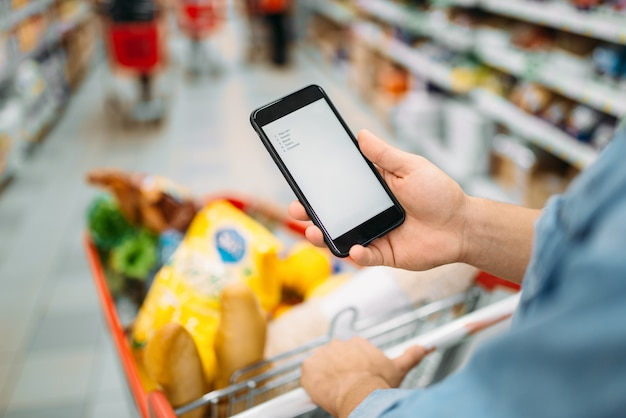 Man with trolley makes a purchase by the list on phone in supermarket. male customer in shop, don't forget to buy concept
