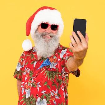 トロピカルシャツとコピースペースのクリスマス帽子を持つ男