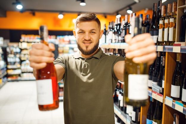 Человек с двумя бутылками алкоголя в продуктовом магазине