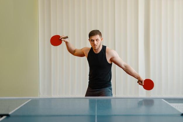 Человек с двумя ракетками, играя в пинг-понг в помещении.
