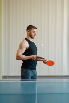 Man with two rackets stuffs blows in ping pong indoors.