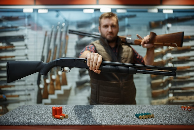 Человек с двумя винтовками за прилавком в оружейном магазине