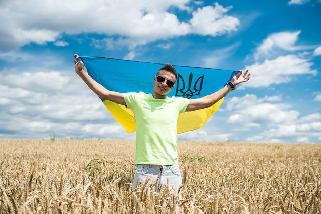 夏の麦畑にウクライナの旗を持つ男。ライフスタイル