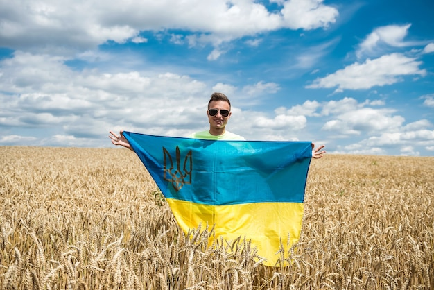 Man with ukrainian flag on wheat field in summer. lifestyle