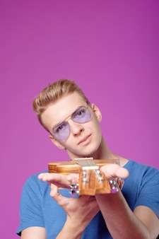 Man with ukulele in hands on purple background