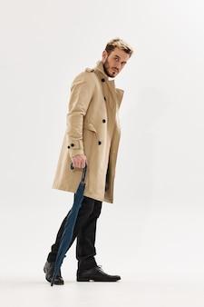 傘の秋のスタイルのポーズをとる服のフルレングスの男。高品質の写真
