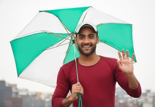 Человек с зонтиком портрет красивого индийского мужчины