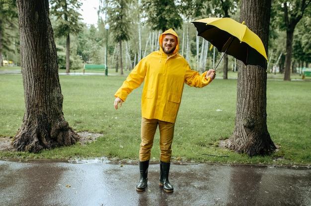風の強い雨の日に夏の公園を歩いている傘を持つ男。レインケープとゴム長靴の男性、路地の雨天