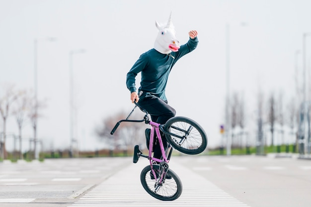 Man with unicorn mask riding a bicycle
