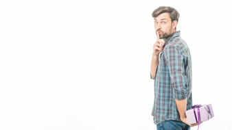 Man with valentine gift making silence gesture on white background