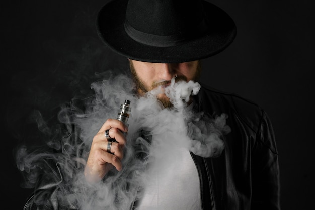 Man with vaping mod exhaling steam at black studio . bearded guy smoking e-cigarette to quit tobacco. vapor and alternative nicotine free smoking concept