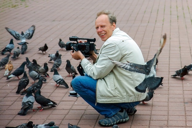 A man with a video camera attracted a flock of pigeons