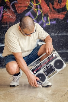 Man with a vintage boombox sitting on street next to a wall with graffiti