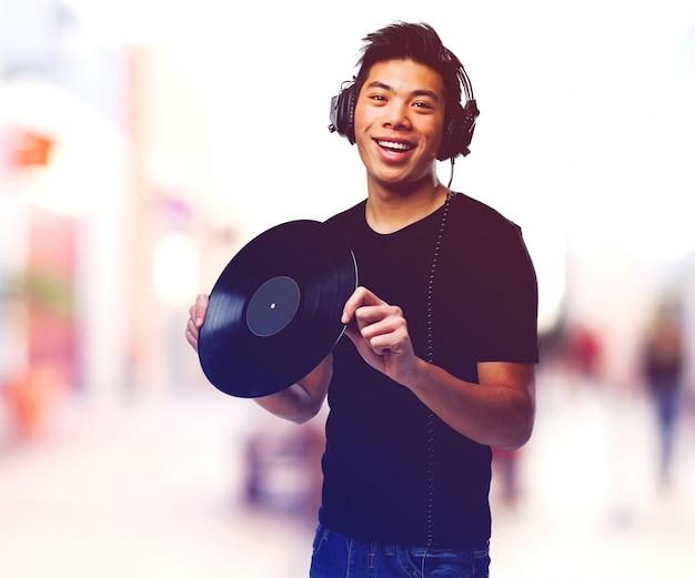 ビニールレコードやヘッドフォンを持つ男