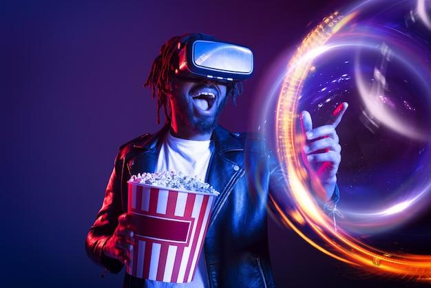 Мужчина в очках vr и попкорном смотрит 3d-фильм