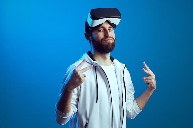 Человек в очках vr на лбу показывает жест мира на синем фоне