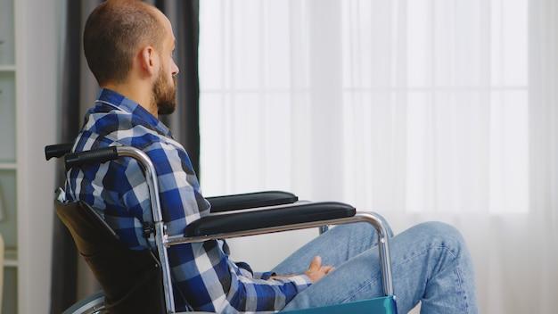 車椅子で悲しそうに座っている歩行障害のある男性。