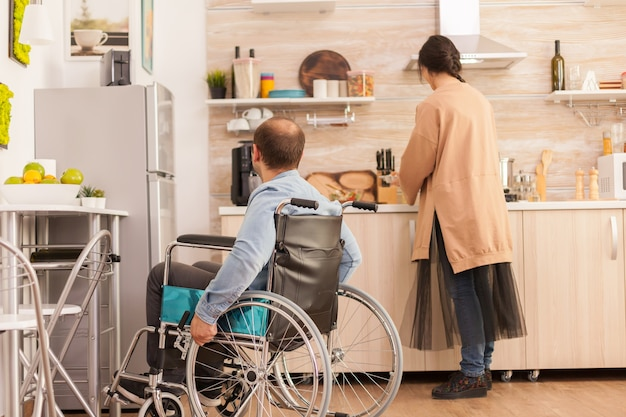Man with walking handicap in wheelchair looking at wife how she's cooking. disabled paralyzed handicapped man with walking disability integrating after an accident.