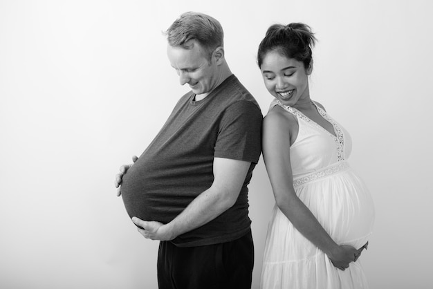 Man with watermelon as stomach and pregnant asian woman together as multi ethnic married couple in black and white
