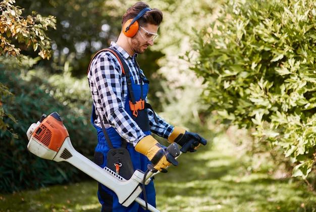 草を刈る雑草ワッカーを持つ男