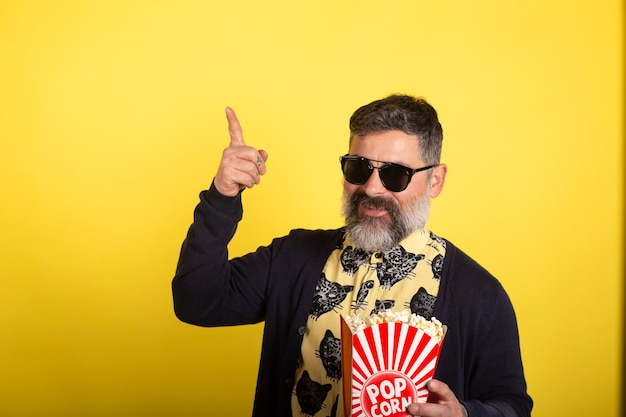 Man with white beard and sunglasses on isolated yellow background holding a large bucket of popcorn while pointing up.