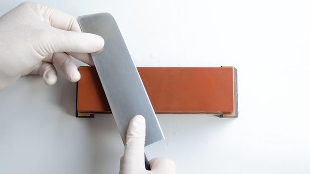 Человек с белыми перчатками точит японский нож накири с точилкой точильного камня или точильного камня на белом пространстве
