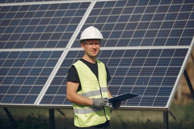 Человек с белым шлемом возле солнечной панели