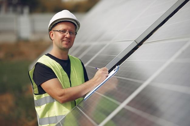 태양 전지 패널 근처 흰색 헬멧을 가진 남자