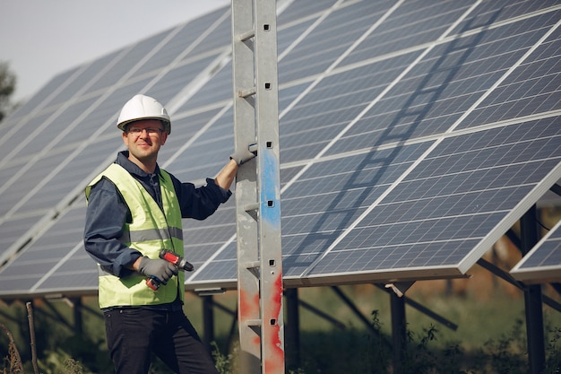 Man with white helmet near a solar panel