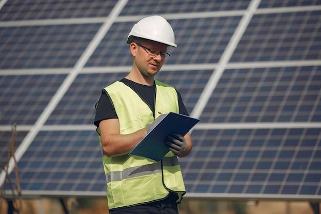 Man with white helmet near a solar panel