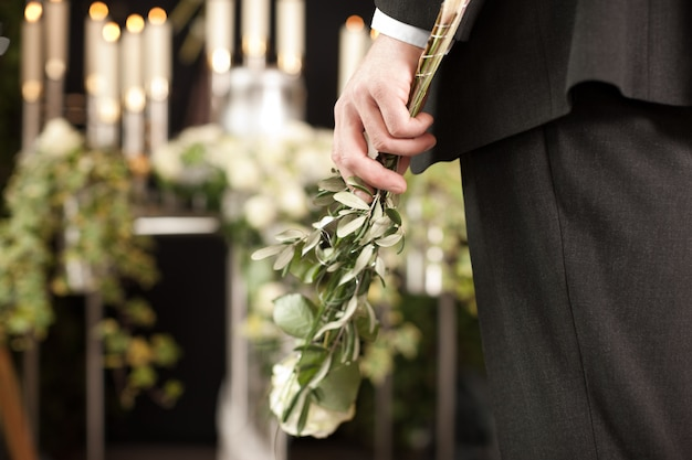 Man with white roses at funeral
