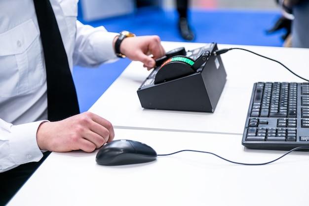 Человек с белой рубашкой перед компьютерным операционным контроллером, клавиатурой