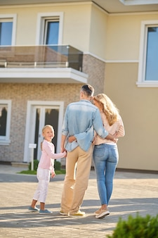 Man with wife and daughter admiring new home