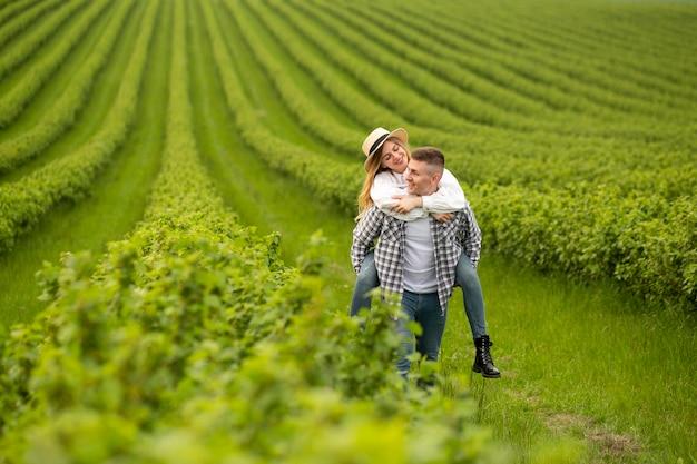 農場でのピギーバックライドの妻を持つ男