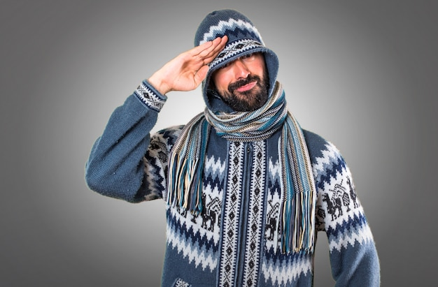 Man with winter clothes saluting on grey background