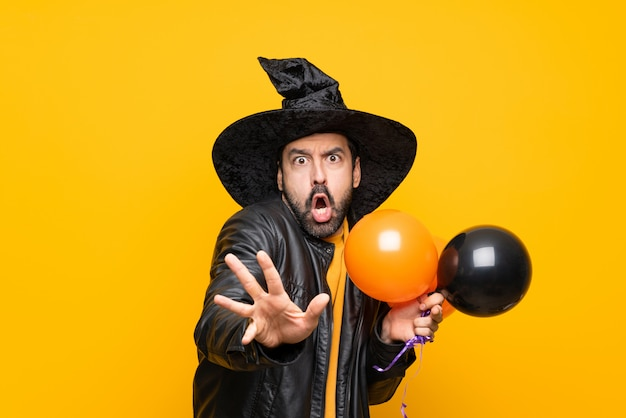 Man with witch hat holding black and orange air balloons for halloween party nervous stretching hands to the front