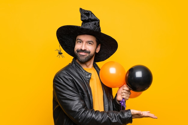 Man with witch hat holding black and orange air balloons for halloween party presenting an idea while looking smiling towards