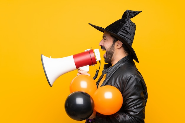 Man with witch hat holding black and orange air balloons for halloween party shouting through a megaphone