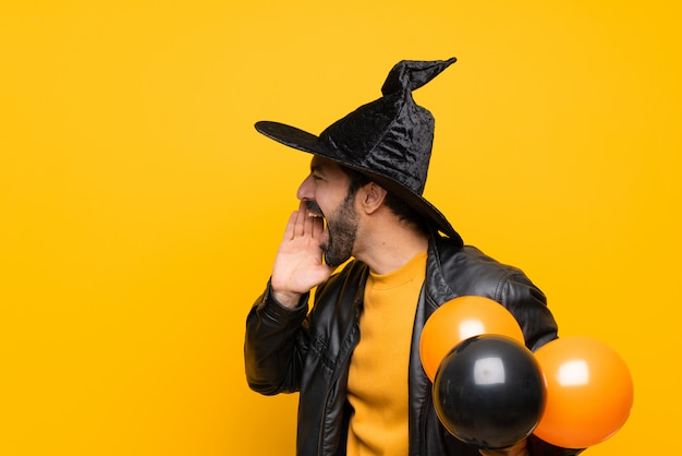 Man with witch hat holding black and orange air balloons for halloween party shouting with mouth wide open to the lateral