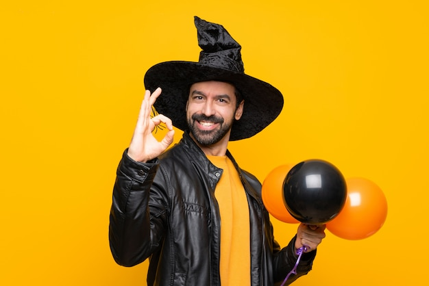 Man with witch hat holding black and orange air balloons for halloween party showing ok sign with fingers