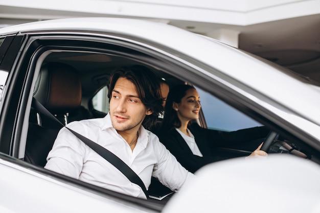 Uomo con la donna in una sala d'esposizione dell'automobile che sceglie un'automobile